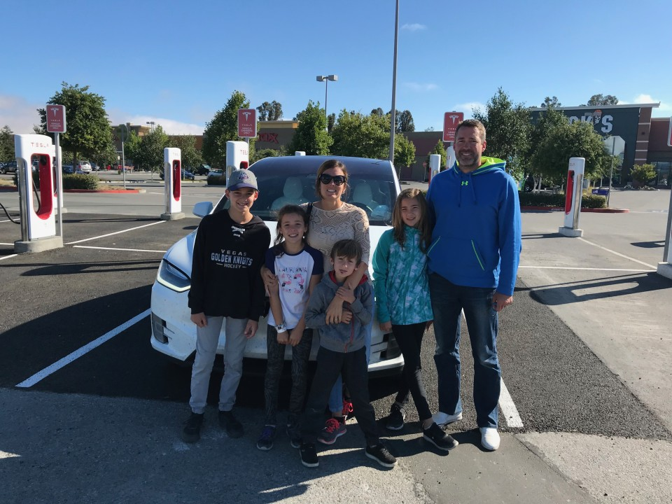 Eric and his family posing in front of an electric car