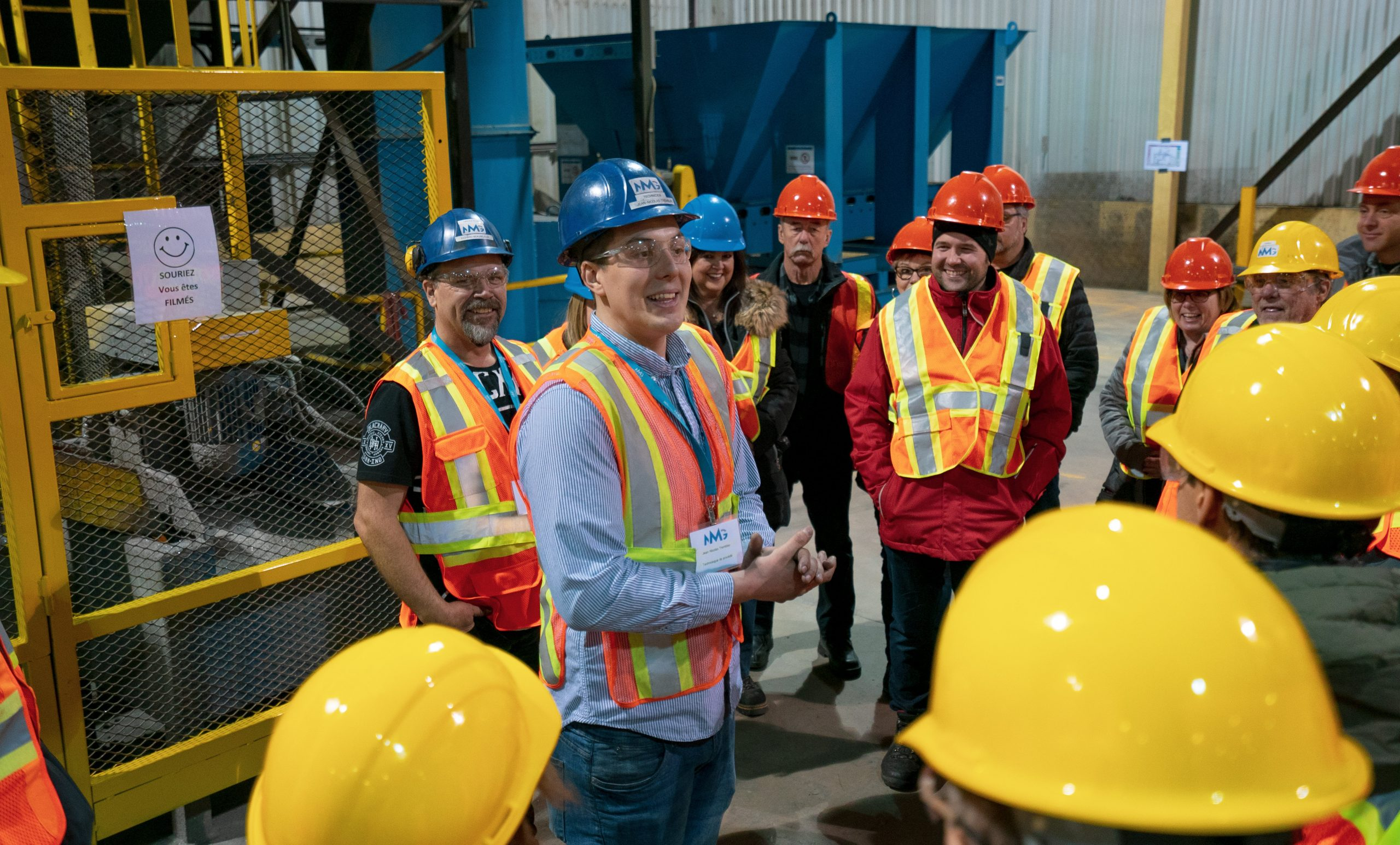 Smiling employees dressed in helmets and protective vests gathered for a meeting in a production plant.