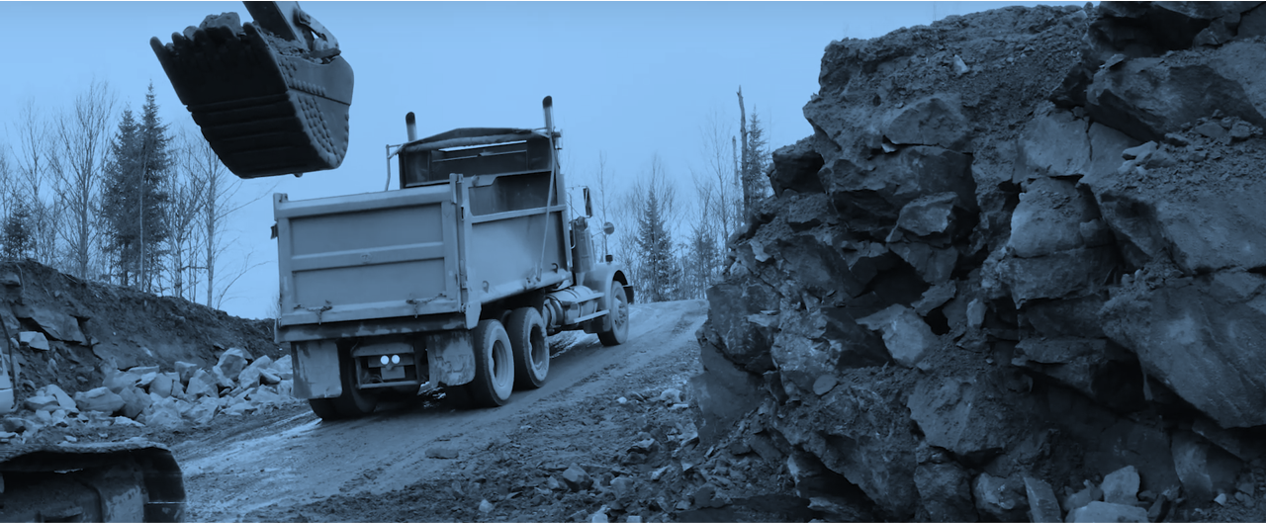 Excavator and truck on a mining site with blue filter