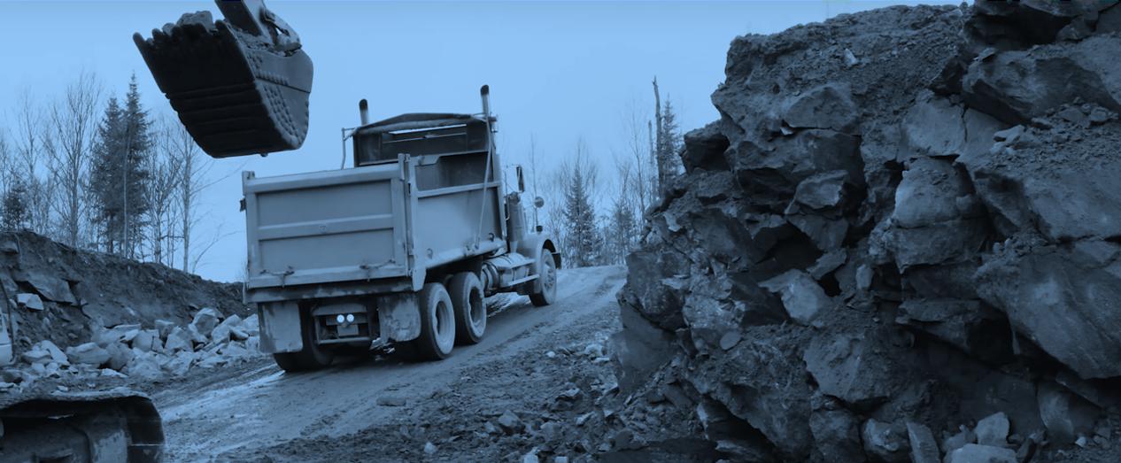 Pelle mécanique et camion sur un terrain d'exploitation minière avec filtre bleu