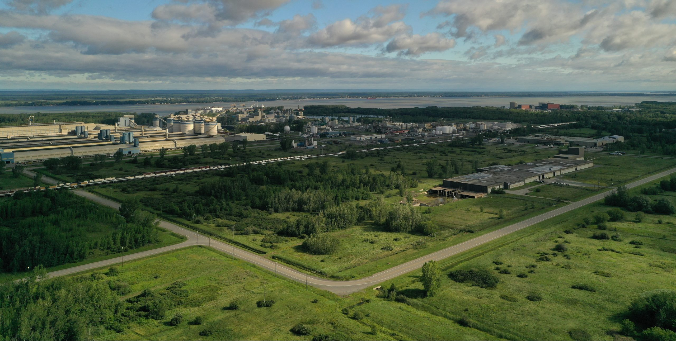 Far photo of grassed fields and a factory