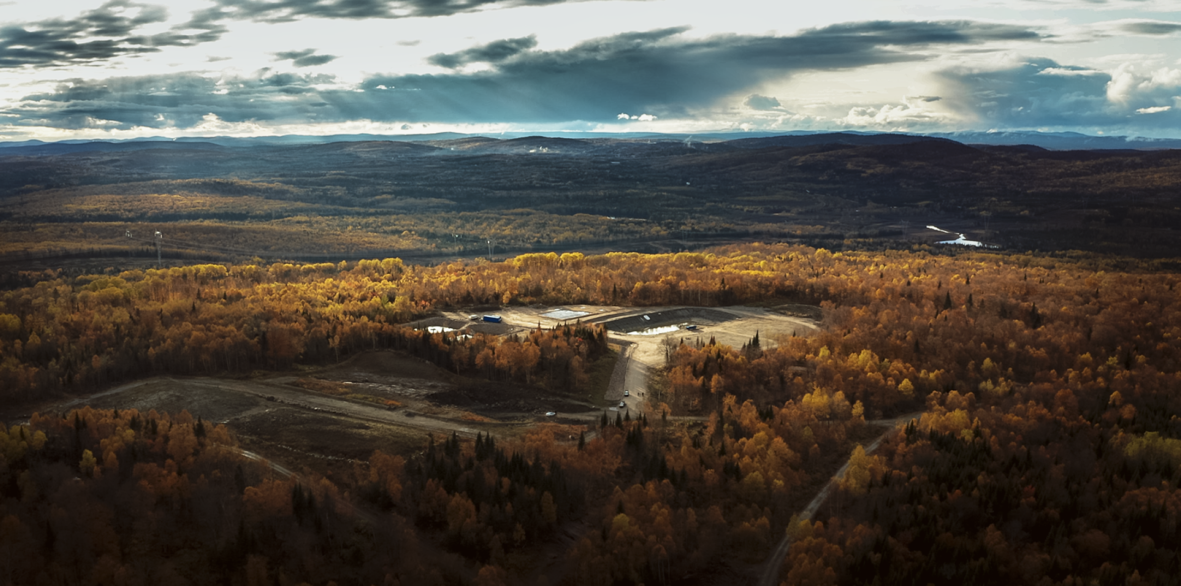 Far photo of a mine site surrounded by trees in the fall