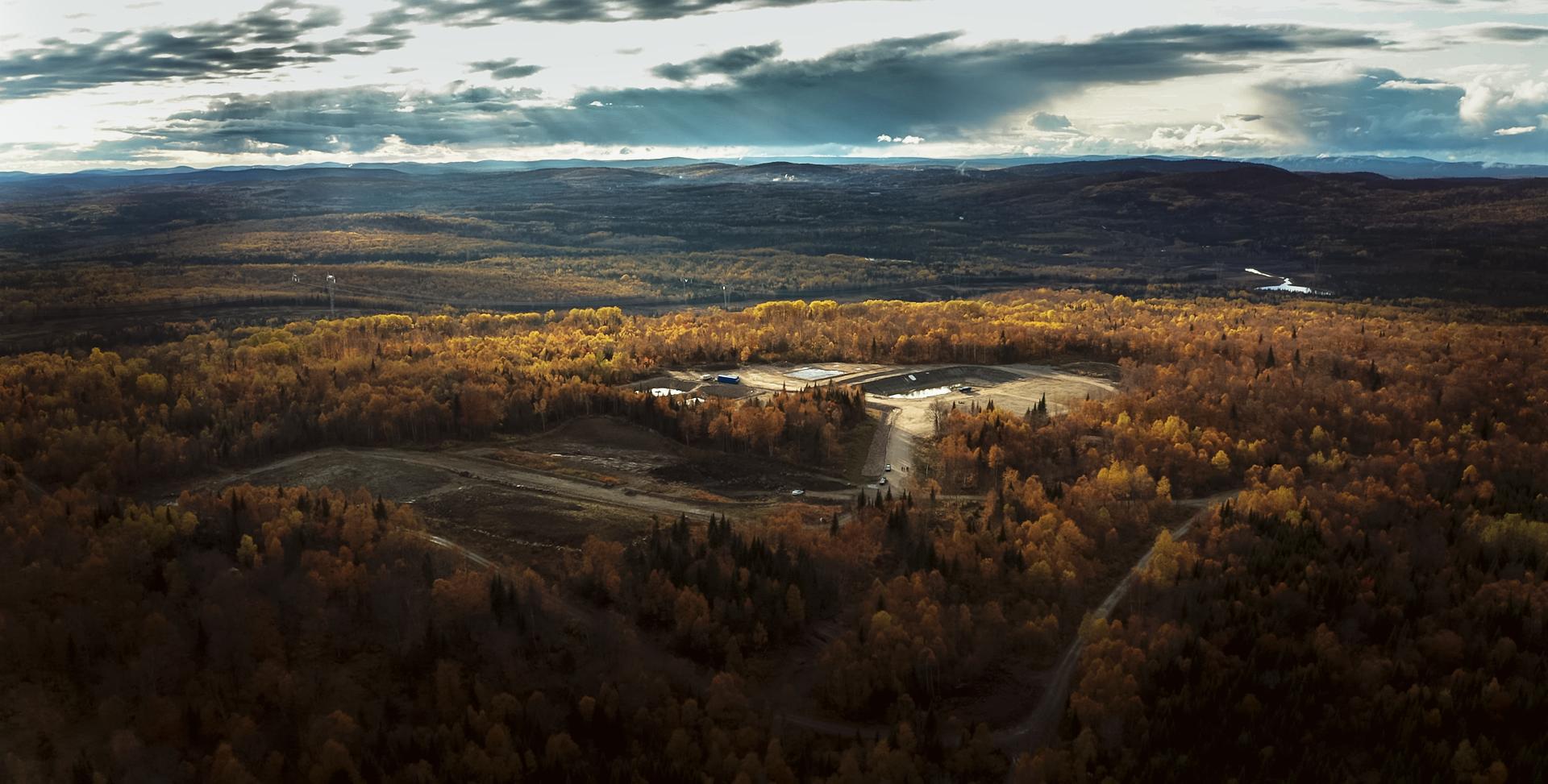 Photo d'une mine vue de loin dans un paysage d'automne en fin de journée