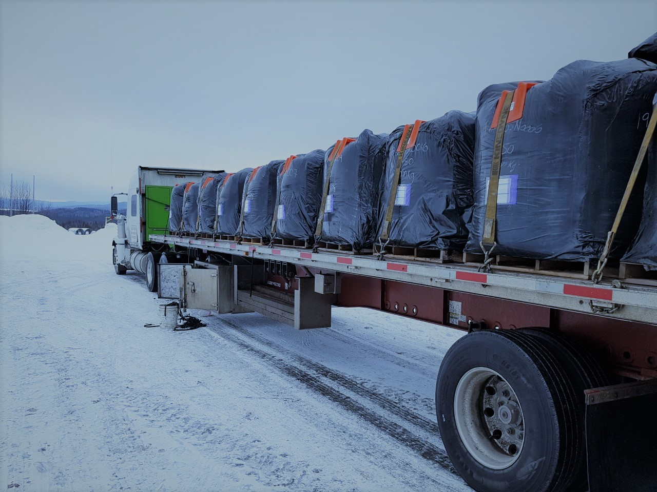 Truck loaded with graphite packed on a snow-covered road