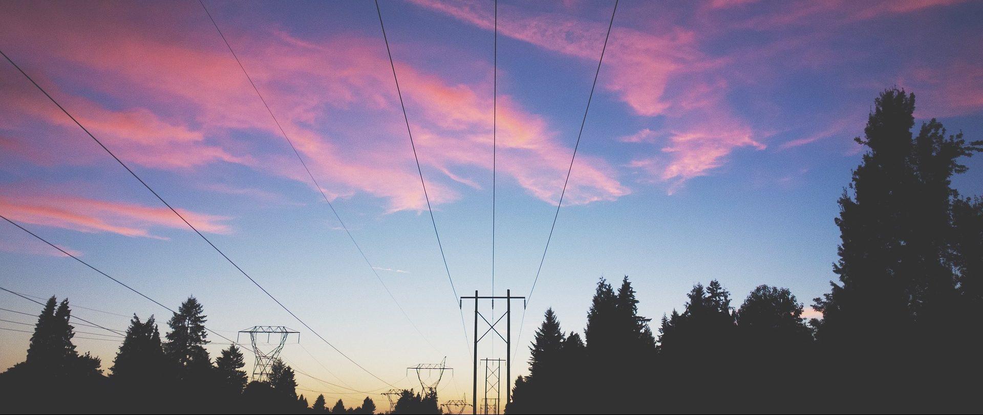 Vue vers le haut de lignes électriques et pylônes devant un ciel rose