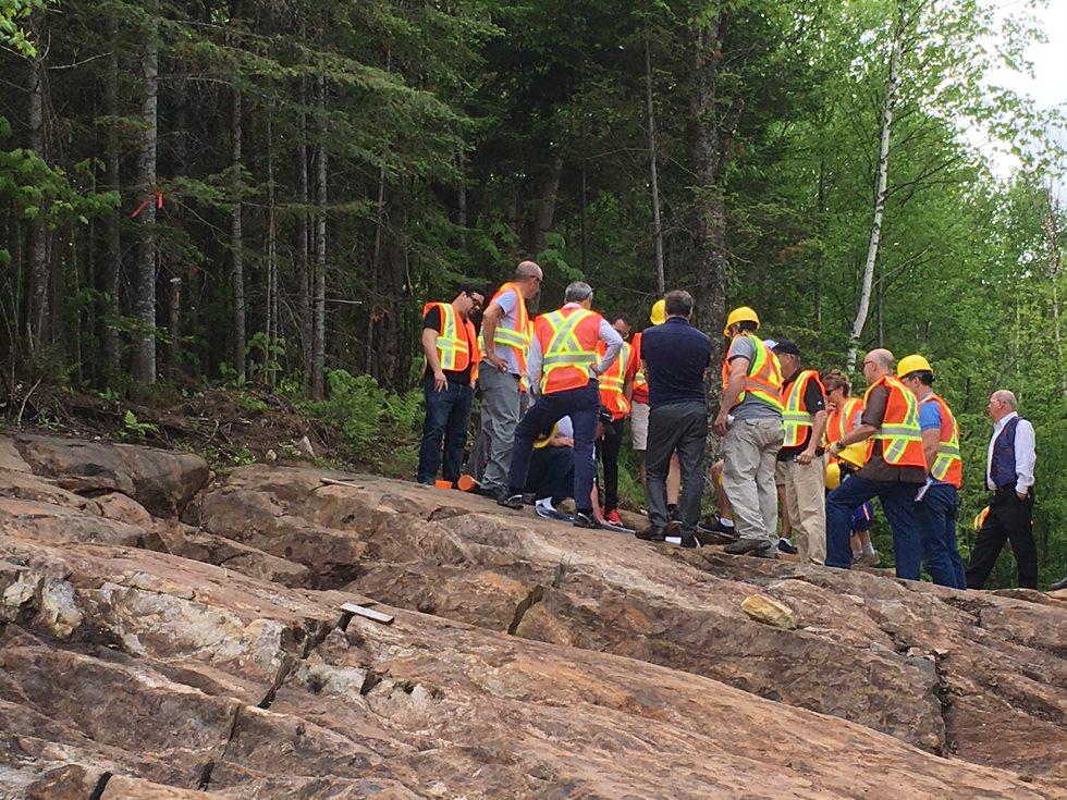 Hommes et femmes portant des gilets et des casques de sécurité regroupé sur une roche près d'une forêt